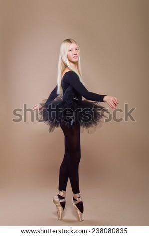 Portrait of the ballerina in ballet pose. Teen girl, blonde. Beige background - stock photo