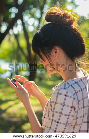 Portrait of the beautiful asian girl playing mobile phone alone in the garden,vintage tone