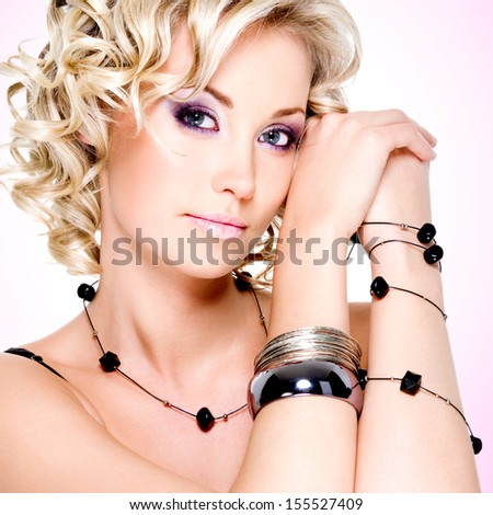 Portrait of the beautiful blond woman with curly hairstyle posing at studio - stock photo