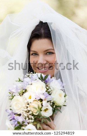 Portrait of the beautiful bride in a snow-white veil with a bouquet - stock photo
