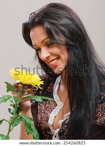 Portrait of the beautiful brunette girl with healthy long hair, holding in hand yellow flower.  - stock photo