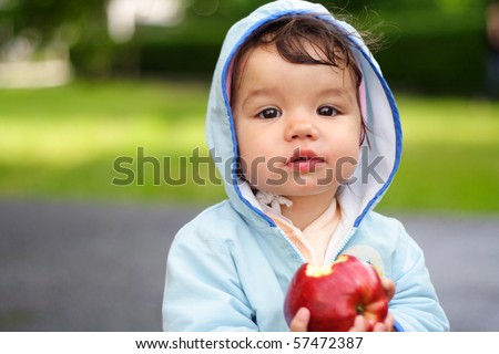 portrait of the beautiful child holding an apple - stock photo