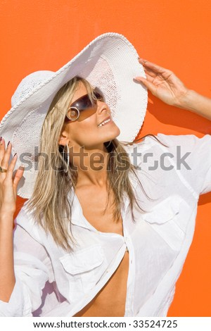 Portrait of the beautiful cute girl in white clothes and a hat on an orange background - stock photo
