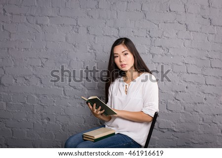 Portrait of the beautiful elegant girl student in jeans and a white jacket Asian appearance in a studio on a dark background sitting on a chair