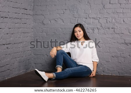 Portrait of the beautiful elegant girl student in jeans and a white jacket Asian appearance in a studio on a dark background sitting on a chair standing at the brick wall