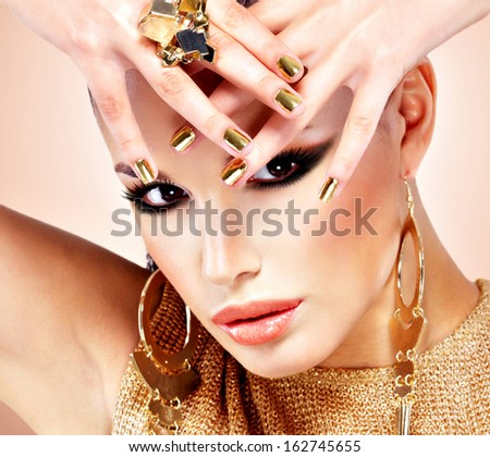 Portrait of the beautiful fashion woman with black makeup and golden manicure - stock photo