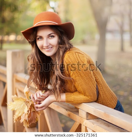 Portrait of the beautiful fashionable woman outdoor on sunny autumn day. - stock photo