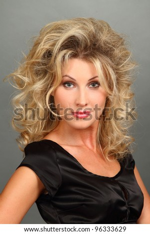 Portrait of the beautiful girl-blonde in a black dress with a magnificent hairdress. Looks in a lens. close up.