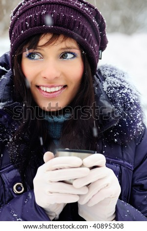 Portrait of the beautiful girl drinking hot beverage in snowy winter. - stock photo
