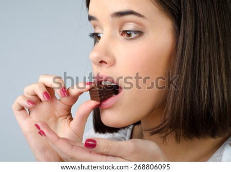 Portrait of the beautiful girl eating chocolate cookies isolated on gray background. - stock photo