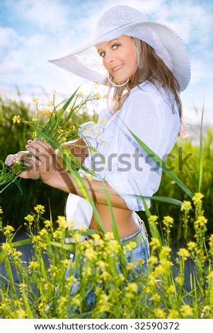 Portrait of the beautiful girl in a white hat with field flowers - stock photo