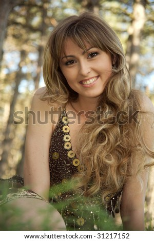 Portrait of the beautiful girl on a background of green trees.