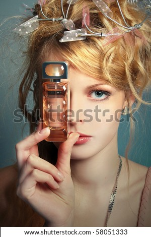 Portrait of the beautiful girl with a bottle of perfume about her face