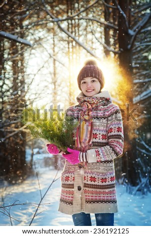Portrait of the beautiful girl with a fir-tree branch in hands in the winter wood