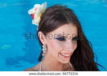 Portrait of the beautiful girl with a flower in hair against blue water