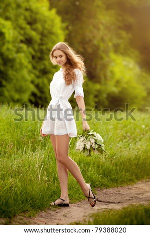 Portrait of the beautiful girl with a flower lilac - stock photo