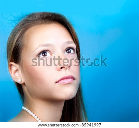 Portrait of the beautiful girl with a gentle face skin and a pleasant sight against the blue sky. - stock photo