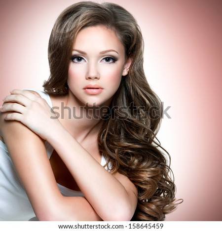 Portrait of  the  beautiful girl with  long curly hairs posing at studio and looking at camera