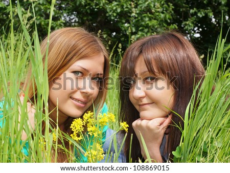 Portrait of the beautiful girls in a yellow flowers - stock photo