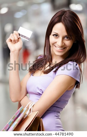 Portrait of the beautiful happy girl in the shop, holding in a hand a credit card