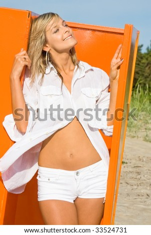 Portrait of the beautiful happy girl in white clothes on an orange background - stock photo