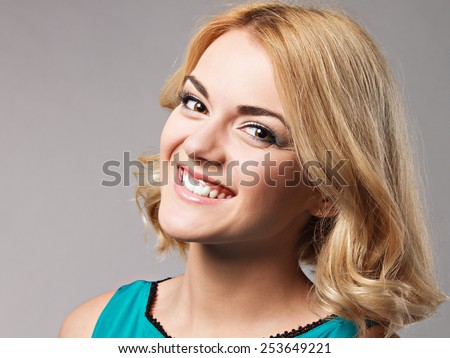 Portrait of the beautiful happy smiling girl posing in studio on grey background.