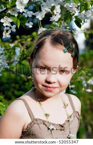 Portrait of the beautiful little girl in spring garden