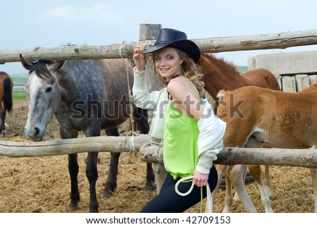 Portrait of the beautiful rural girl on a background horses