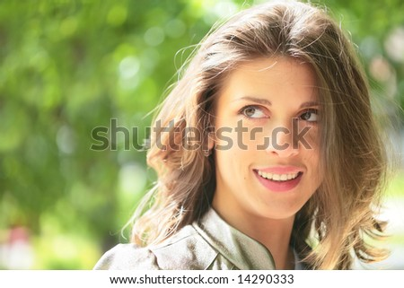 portrait of the beautiful smiling girl with brown hair shining under sunlight