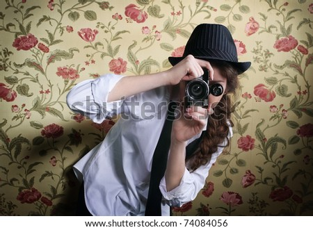 Portrait of the beautiful stylish brunette woman with old camera - stock photo