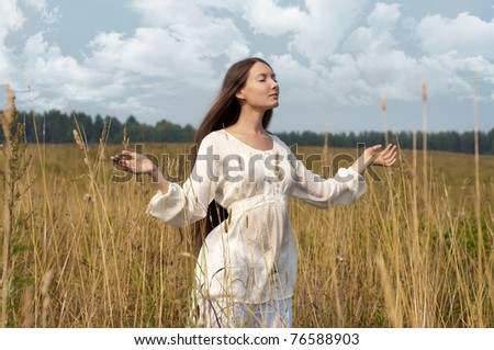 Portrait of the beautiful woman at the field. Rural style - stock photo