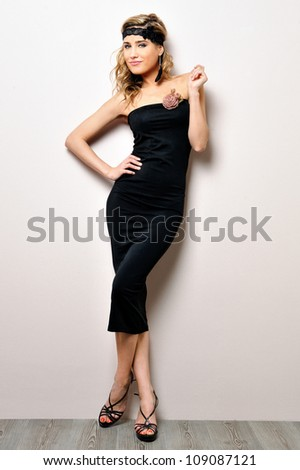 Portrait of the beautiful woman in a black dress. Studio shooting.