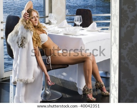 Portrait of the beautiful woman in a luxuriant restaurant at the water - stock photo