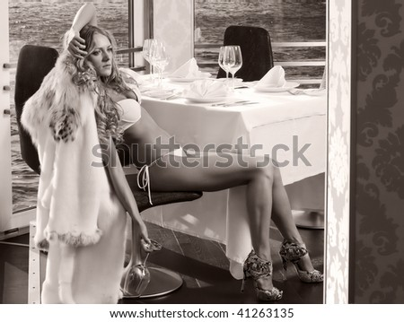 Portrait of the beautiful woman in a restaurant at the water. Monochrome. - stock photo