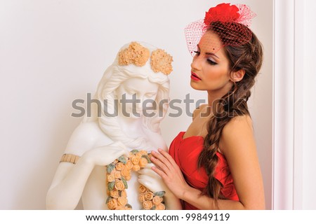 Portrait of the beautiful woman in red dress standing near the antique statue. - stock photo