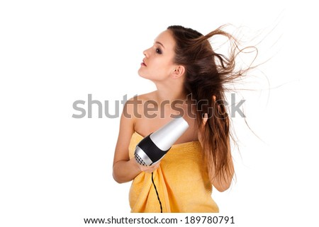 portrait of the beautiful woman in towel, keeping hairdryer, white background - stock photo