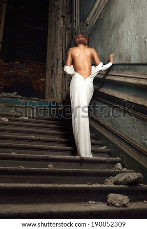 portrait of the beautiful woman in white dress with naked back. She is going upstairs. Studio with interior of old palace. Not necessary property release. - stock photo