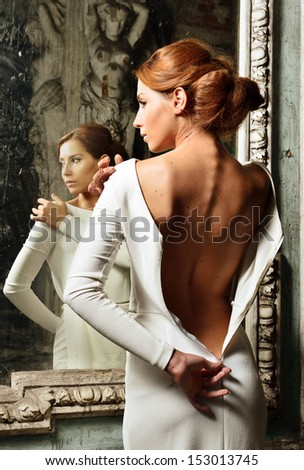 Portrait of the beautiful woman in white dress with naked back. She is standing at the mirror. Studio with interior of old palace. Not necessary property release. - stock photo