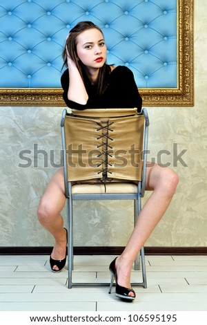 Portrait of the beautiful woman sitting on the chair in a beautiful interior. - stock photo