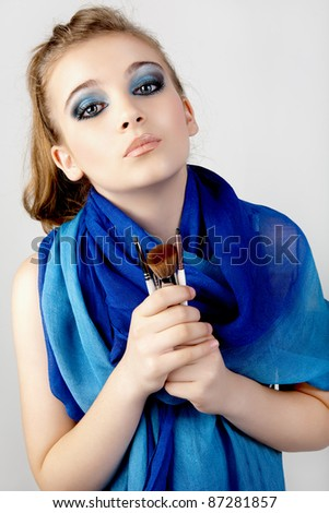 Portrait of the beautiful woman with make-up brushes. - stock photo