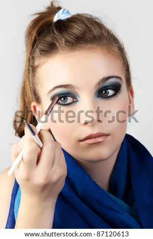 Portrait of the beautiful woman with make-up brushes near attractive face. - stock photo