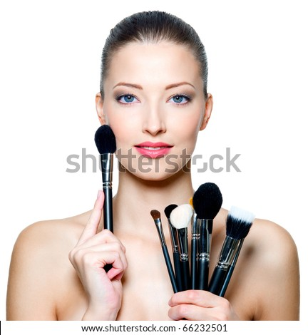 Portrait of the beautiful woman with make-up brushes near attractive face. Adult girl posing over white background - stock photo