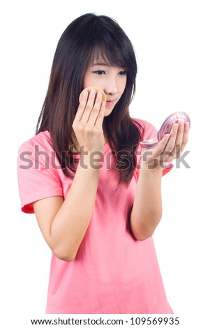 Portrait of the beautiful young asianwoman applying makeup on white background
