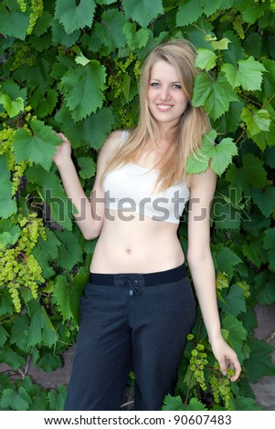Portrait of the beautiful young blonde with grapes on a green background of foliage