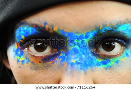 Portrait of the beautiful young girl in bright multi-coloured mask with scarf on her head - stock photo