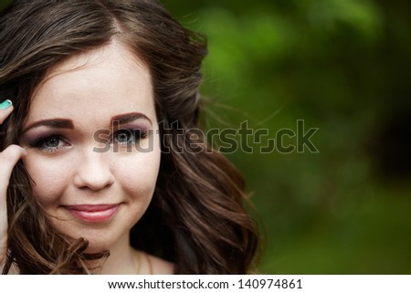Portrait of the beautiful young girl on green background