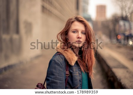 Portrait of the beautiful young girl on the city street - stock photo