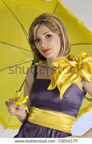 Portrait of the beautiful young girl under a yellow umbrella - stock photo