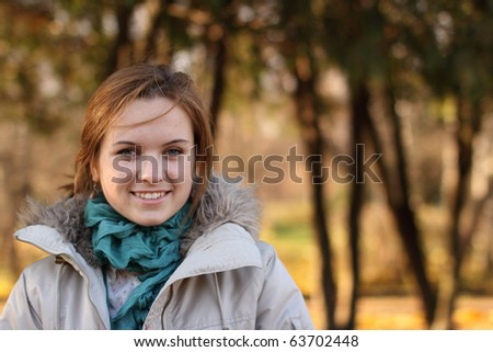 Portrait of the beautiful young girl walking in autumn park