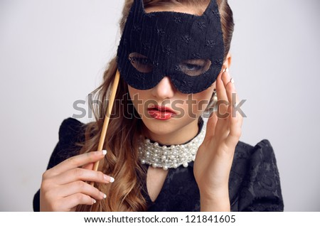 portrait of the beautiful young woman in a mask - stock photo